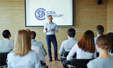 Instructor giving a group talk with CSA Group logo on projector screen.